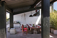 Billiard table lights hang above an outdoor dining area located in the shade on one side of the house