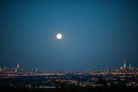 The Blue moon rises between the Empire State Building and One World Trade Center while it is seen from New Jersey.  07/31/2015. Eduardo MunozAlvarez/VIEWpress
