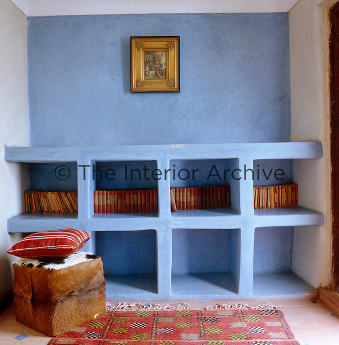 These simple baked-mud units, painted Moroccan blue, provide ample storage along one wall of the living room