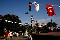 ISTANBUL - MAY 28, 2007:   A man hangs the Turkish National flag in prepartion for a National Parade.  Istanbul, Turkey. Photo by Landon Nordeman.