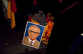 Berlin, Germany<br /> October 3, 1990<br /> <br /> East German souvenirs are sold on the streets as East and West Germany are reunited on this night. A picture of Erich Honecker, who  was a German Communist politician who led the German Democratic Republic (East Germany) from 1971 until 1989 is displayed.<br /> <br /> Large crowds gathered for the event, nearly one year after the Berlin Wall was opened allowing East Germans to travel freely to the West. By October 1990 almost nothing remained of the wall.