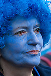 A lady with her face painted blue watches the speakers. (Images free for Editorial Web usage for Fresh Air Participants during COP 15. Credit: Robert vanWaarden)