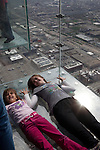 Two girls lie on the Ledge at the Willis Tower Skydeck to have their picture taken, Chicago, IL