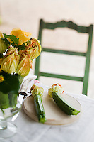 Fresh courgettes with their bright yellow flowers are bunched in a glass vase to create an unusual arrangement