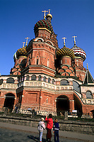 Russia Moscow the famous St Basils Cathedral with tourists in Red Square.