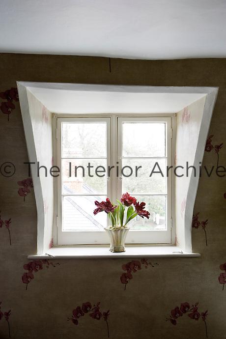 Purple flowers in bedroom window mirror the floral print wallpaper