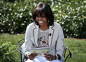 "First lady Michelle Obama reads the story ""Cloudy with a Chance of Meatballs"" to children during the annual White House Easter Egg Roll on the South Lawn of the White House April 1, 2013 in Washington, DC.  President Barack Obama and first lady Michelle Obama hosted thousands of people during the annual celebration of Easter.  .Credit: Alex Wong / Pool via CNP"