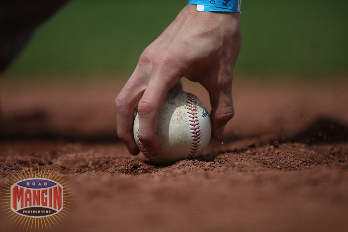 SAN FRANCISCO, CA - JUNE 3:  Detail of a Pittsburgh Pirates bat boy picking up a baseball on the dirt warning track behind home plate during the game against the San Francisco Giants at AT&T Park on Wednesday, June 3, 2015 in San Francisco, California. (Photo by Brad Mangin)