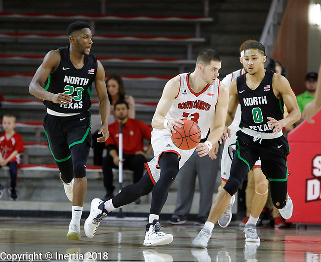 VERMILLION, SD: MARCH 14:  Matt Mooney #13 of South Dakota drives on Ryan Woolridge #0 of North Texas during the 2018 CBI Basketball Tournament at the Sanford Coyote Sports Center in Vermillion, S.D. Michael Miller #23 of North Texas is at left. (Photo by DIck Carlson/Inertia)