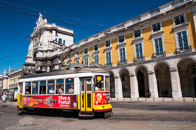 A typical streetcar (trolley) exiting the Commerce Square (Praca do Comercio) in Lisbon, Portugal. Although Lisbon has a modern fleet of trams, climbing the steep hills and narrow streets of Lisbon is mostly done in small streetcars, that remain faithful to their style since their first uses in the city, including even the wooden benches and driving system inside.