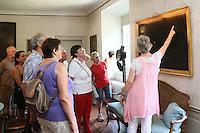 Museumsführerin Andrea Rohrmann (M., rosa) zeigt der Gruppe der Leser-Radtour ein über die Jahre verdunkeltes Gemälde des Malers Seekatz im Jagdschloss Kranichstein