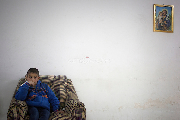 15/11/14. Alqosh, Iraq. Milad rests on a chair in the hallway of the orphanage after playing with his friends.