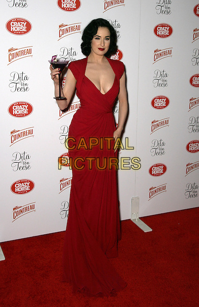 DITA VON TEESE .Opening Night at MGM Grand's Crazy Horse Paris inside the MGM Grand Resort Hotel and Casino, Las Vegas, Nevada, USA, 31st March 2010..full length red dress long maxi low cut cleavage hand holding drink cocktail martini glass shoulder pads .CAP/ADM/MJT.©MJT/Admedia/Capital Pictures