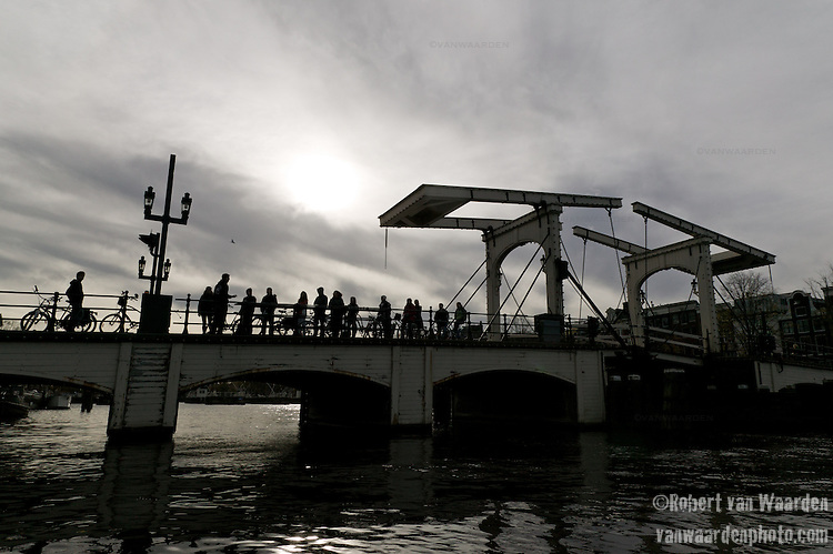 A group of tourists and cyclists enjoy the view on the Magere Brug over the Amstel river in Amsterdam late in the afternoon.