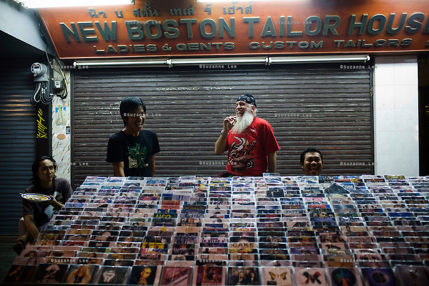 Jonathan Isaac Newman jokes around with Thai nationals at the pirated CD stalls in Khao San as he heads out for a party in Bangkok after Chanuka celebrations at Chabad Bangkok (Khao San), Thailand on 12th December 2009. He has just moved in this week and lives alone..Jon, an Irish/American, is a jeweller by profession, owns a video game manufacturing company in the USA, and used to work for the FBI. His brother is a rabbi. Jon has 4 children with his ex-wife, an Israeli. He speaks 7 languages and has recently decided to live to Bangkok. People often mistake Jon for a rabbi in Chabad Khao San because he wears a black coat and hat. However, soon after prayers, Jon changes into t-shirt and jeans, carrying his prayer clothes in a bag with him as he walks home..Photo by Suzanne Lee / For Chabad Lubavitch