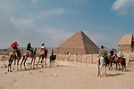 CAIRO - NOVEMBER 30, 2004 : Tourists on camel and horses visit the 5000 years old Giza pyramids in Cairo, on November 30, 2004. Situated high on a desert plateau overlooking sprawling Cairo, Giza is the most visited tourist site in Egypt ,with the Sphinx and the 481ft high great Pyramid. Tourism has been on the decline in Egypt following a series of terrorist attacks targeting foreign tourists. (Photo by Jean-Marc Giboux)