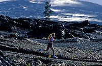 Young woman running on the lava fields at Volcanoes National Park
