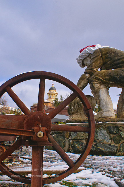 Statue of gold miner Claude Chana in the snow, with the historic Auburn Courthouse in the background, Auburn, California.