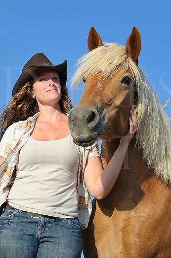 Cowgirl and palomino horse long with blonde mane, a happy country girl with her animal in summer sunshine and blue skies, casual western clothing, Pennsylvania, PA, USA.