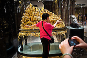A tourist poses for a photo in front of a gold sculpture at the Grand Lisboa Hotel in Central Macau, China.