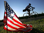 A lone early morning rider rolls past an American flag-lined roadway entering Ogden.
