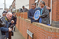 Community Organisers pose for media with the Malcom X Blue Plaque prior to being afixed to the building wall