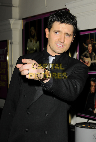 "TOM CHAMBERS.The ""Cinderella: Shoe Must Go On"" Festive fundraiser in aid of Starlight Children's Foundation..Piccadilly Theatre, Shaftsbury Avenue, London, England.22nd December 2008.portrait headshot black jacket shirt pointing watch.CAP/CAN.©Can Nguyen/Capital Pictures."