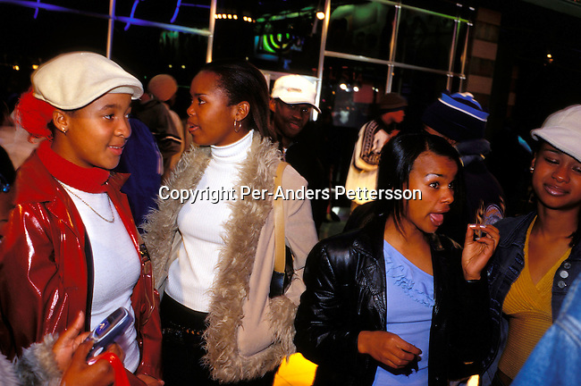 dippnig00064 Nightlife JOHANNESBURG, SOUTH AFRICA - MAY 28: Unidentified young girls on May 28, 2002 at The Zone, a trendy shopping mall and gathering point for youth in Rosebank a suburb in Johannesburg, South Africa. He comes here on the weekends to hang out with other youth, black and white, and to check out the latest fashion clubs etc. After eight years into democracy a new black middleclass and elite is growing, and they have money to spend on houses, cars and entertainment. .©Per-Anders Pettersson/iArika Photos...
