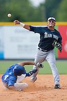 Second baseman Cesar Fuentes #23 of the Pulaski Mariners turns a double play as Derek Rodriguez #4 of the Burlington Royals slides into second base at Burlington Athletic Park August 4, 2009 in Burlington, North Carolina. (Photo by Brian Westerholt / Four Seam Images)