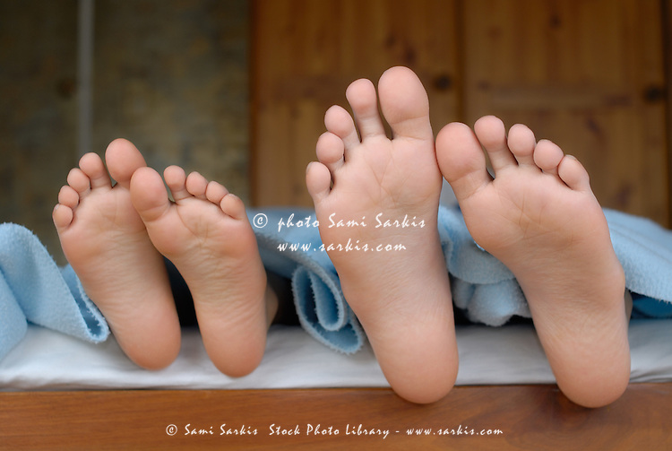 Two children (6-12) lying in bed, focus on feet, close-up