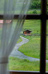 Path leading to wooden farm shed in field, viewed from window.Imst district, Tyrol/Tirol, Austria, Alps.