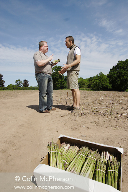 Farmer Andrew Pimbley pictured at his Claremont Farm in Bebington, Wirral, northwest England with chef Paul Askew examining the farmer's annual crop of asparagus. The asparagus is in season in early summer and Claremont Farm supplies local shops, chefs and farmers market with the award-winning product.