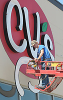 NWA Democrat-Gazette/DAVID GOTTSCHALK Jeremy Alford, with Harrison Sign Company, removes the larger LED channel letters Wednesday, June 6, 2018, of the  CV's Savers Club in Fayetteville. The store is closed and the signage is being relocated to another store.