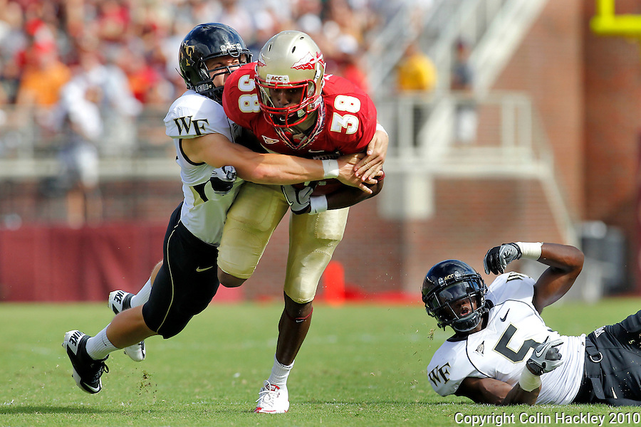 TALLAHASSEE, FL 9/25/10-FSU-WF FB10 CH-Florida State's Jermaine Thomas is wrapped up by Wake Forest's Lee Malchow as Cyhl Quarles watches from the turf during first half action Saturday at Doak Campbell Stadium in Tallahassee. .COLIN HACKLEY PHOTO