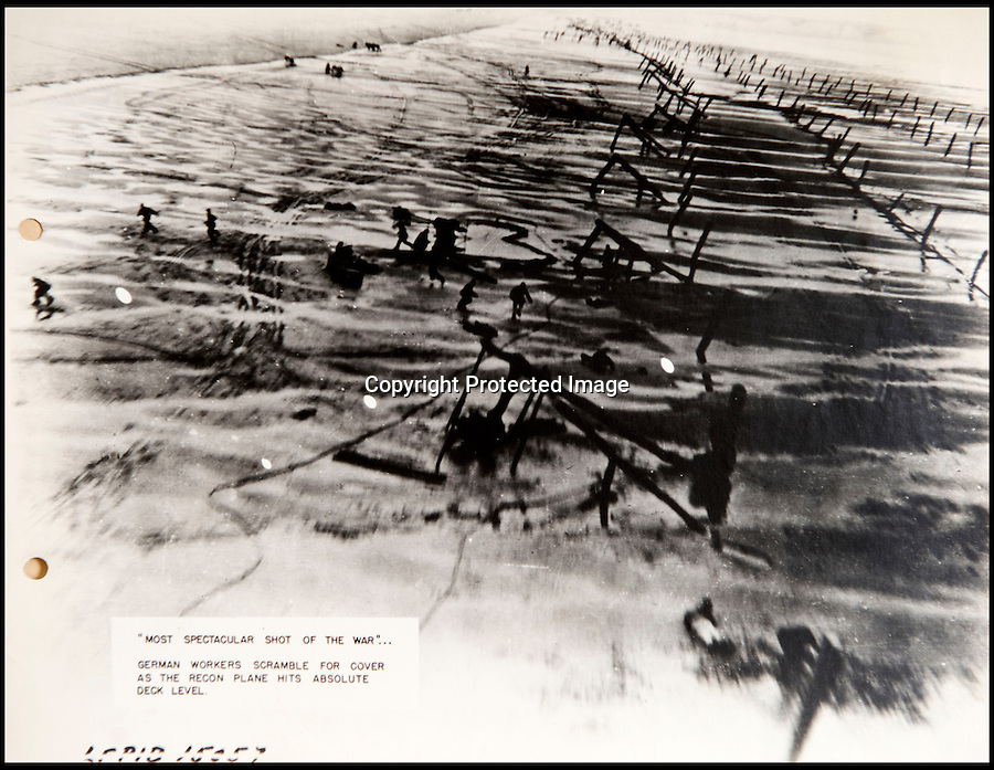 BNPS.co.uk(01202 558833)<br /> Pic: C&TAuctions/BNPS<br /> <br /> 'Most spectacular shot of the War - Germans scramble for cover as recon plane hits absolute deck level...'<br /> <br /> Found in a french flea market - a Top Secret 'how to' guide to D-Day.<br /> <br /> Fascinating top secret documents and photos of the extensive planning that went into the Normandy invasion have emerged after 72 years.<br /> <br /> Incredibly detailed plans of Nazi defences, high resolution photographs, weekly intel reports and even analysis of the German weapons they were likely to face are included in the sale.<br /> <br /> One photo taken at zero feet shows German troops scattering across a beach as a low-level RAF aircraft sweeps by to capture the plethora of anti-landing obstacles.<br /> <br /> Other images show the famous coastline with key cliff-top targets that had to be destroyed either before or on D-Day itself.<br /> <br /> The archive is being sold by C&T Auctions of Kent.