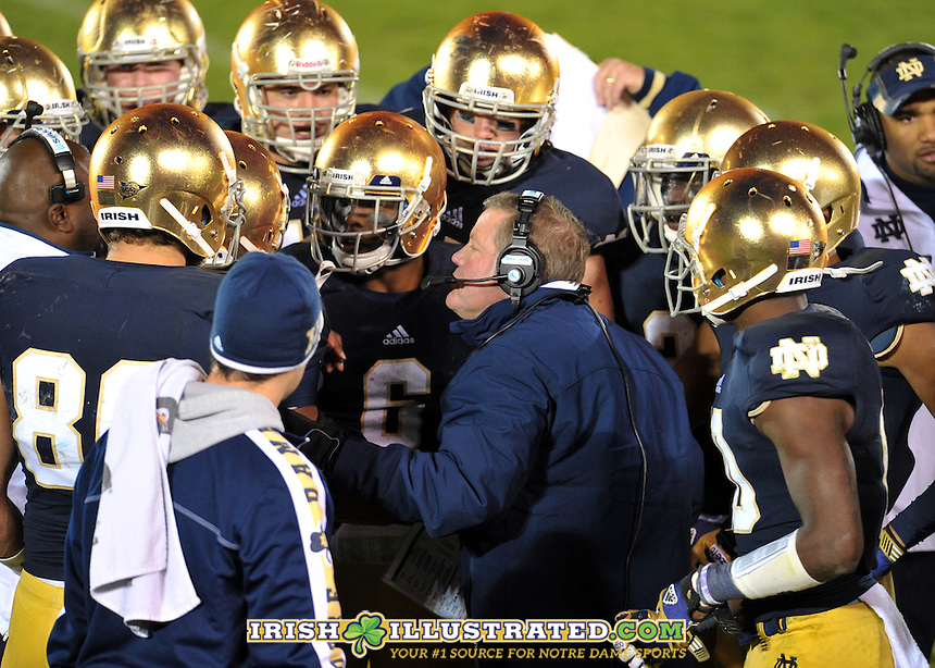 Head coach Brian Kelly huddles with the team.