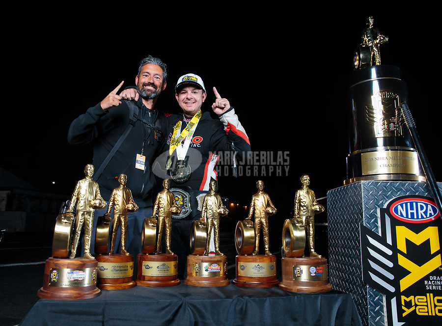 Nov 11, 2018; Pomona, CA, USA; NHRA top fuel driver Steve Torrence poses for a portrait with photographer Jason Zindroski as he celebrates after winning the Auto Club Finals at Auto Club Raceway. Torrence swept all six of the countdown to the championship races to clinch the world championship. Mandatory Credit: Mark J. Rebilas-USA TODAY Sports