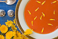 Edible flower (herb), yellow calendula in red tomato soup on blue placemat