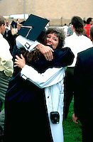 U of St Thomas graduate age 21 and mom 45 hugging after graduation.  St Paul  Minnesota USA