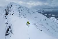 Single female hiker climbs narrow ridge through deep snow on ascent of Matmora mountain peak, Austvågøy, Lofoten Islands, Norway