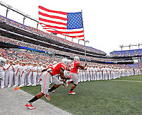 Ohio State Buckeyes defensive tackle Michael Bennett (63) carries out an America flag before the start of their game against Navy Midshipmen at M&T Bank Stadium in Baltimore, Maryland on August 30, 2014. (Dispatch photo by Kyle Robertson)