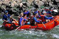 A group of white water rafters brave the wild waters of the Peyete River on board a red inflatable raft. Boise Idaho, Peyete River.