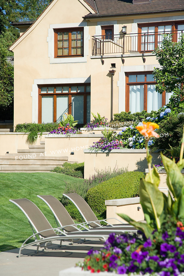 sunny summer image of colorful pink and purple summer annuals spilling out of interesting raised planter boxes built in to a stucco wall that terraces down the back yard of a European-style estate house with blue summer sky above and three poolside lounge chairs lined up between