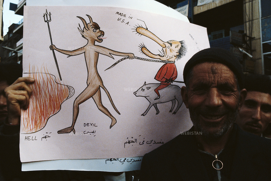 TEHRAN, IRAN - DECEMBER 1979:  A protester standing in front of a caricature drawing. Such caricatures and paintings were used during the hostage crisis at the U.S. embassy in Tehran which was a diplomatic crisis between Iran and the United States where 52 U.S. diplomats were held hostage for 444 days from November 4, 1979 to January 20, 1981, after a group of Islamist students took over the American embassy in support of the Iranian revolution. (Photo by Reza/ Webistan).<br />