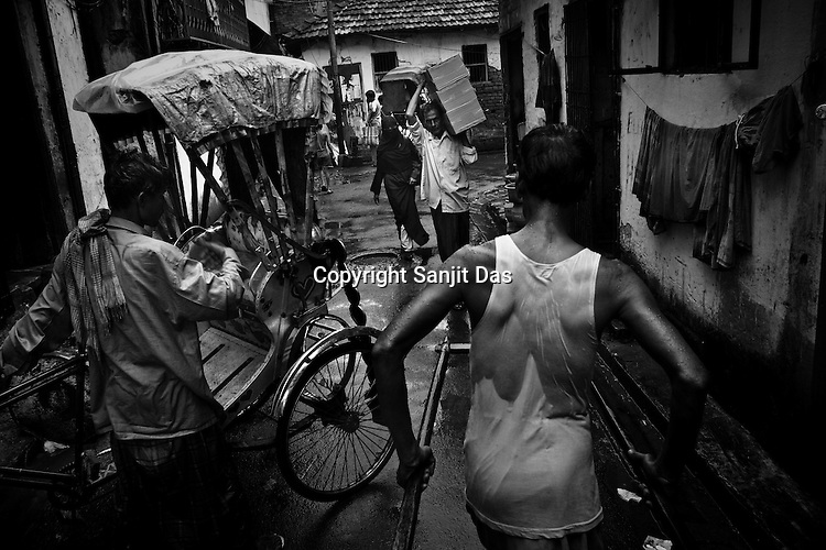 A rickshaw puller takes his customer through the monsoon rain in Calcutta, India. 93 out of every 100 rickshaw pullers are homeless. They sleep after the city sleeps and wake up before everyone else does. Many of them are the sole bread earners for their family. Many plus 40. Many minus any other specialisation for any other job. Of the twenty four thousand rickshaw pullers, only 387 have licenses. .Many rickshaw pullers earn a meagre wage of 100-150 rupees (US $ 2.25-3.5) a day of which they have to give a daily rickshaw rent of 60 (US$ 1.35) rupees to the agent at the end of the day.
