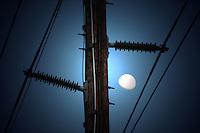 (Mesa, Arizona) The moon is seen through a utility pole one morning in the city of Mesa, Arizona. Photo by Eduardo Barraza © 2013