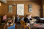 May 8, 2015. Chapel Hill, North Carolina.<br />  Jordan Cates (2nd from left) a graduate student at UNC, enjoys a cup of coffee at Open Eye Cafe. Open Eye is one of the more popular spots for coffee in town. Its sprawling interior allows for reading and studying and people can spend hours there over a drink.<br />  Outsiders tend to lump Chapel Hill with nearby Durham, but the more sensible pairing is with Carrboro, the adjacent town that was once a mere offshoot known as West End. Even today the transition from Chapel Hill, anchored by North Carolina''s flagship public university, into downtown Carrboro is virtually seamless.