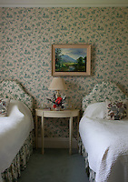 A chinoiserie wallpaper in cream and green covers the walls and upholstery of this twin bedroom