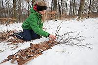 Naturkunst im Winter, Kind, Mädchen legt aus Zweigen und Blättern einen Baum in den Schnee
