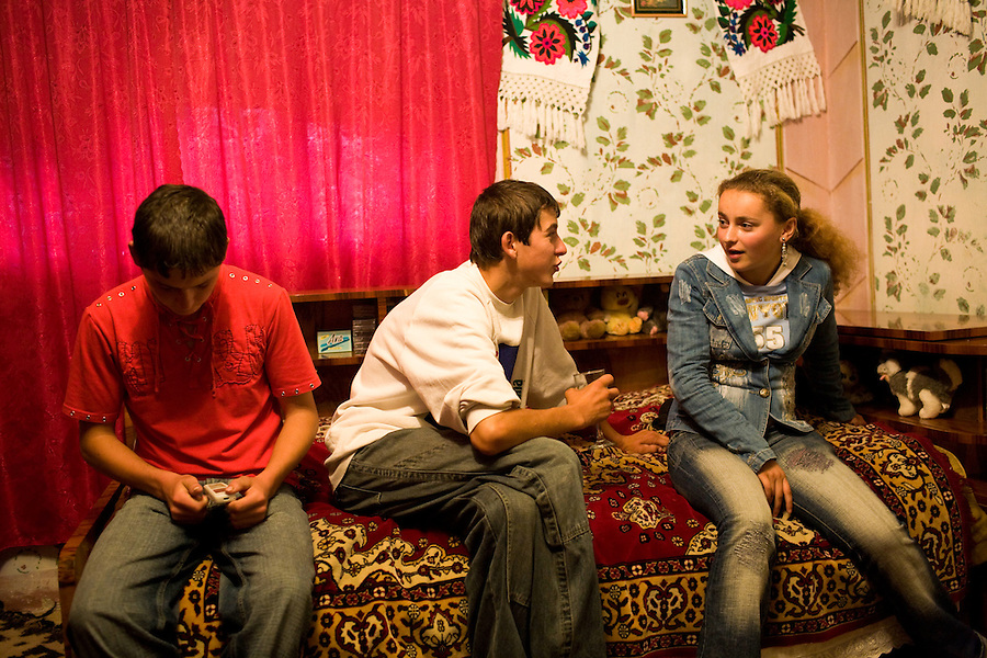 ROMANIA / Maramures / Breb / 03.09.2006 ..Teenagers at a friend's home. Mobile phones and Western fashion are the latest craze even though few houses have running water and traditional village life continues as it has for centuries. ..© Davin Ellicson / Anzenberger